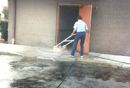 Cleaning an employee grease spill at the back door of a restaurant  .